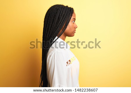 Side view of young African American woman in yellow bikini and sunglasses using laptop sitting on th Stock photo © wavebreak_media