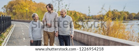 An elderly couple walks in the park with a male assistant or adult grandson. Caring for the elderly, Stock photo © galitskaya