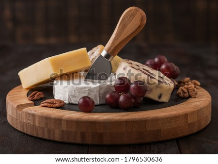 Glass and bottle of red wine with selection of various cheese in wooden box and grapes on wooden tab Stock photo © DenisMArt