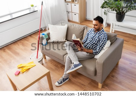 man reading book and resting after home cleaning Stock photo © dolgachov