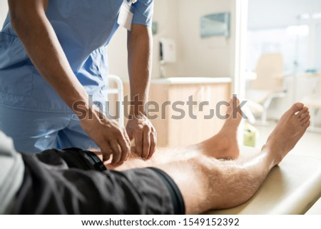 Sick patient lying on couch while clinician in blue uniform massaging his leg Stock photo © pressmaster