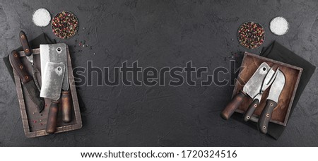 Vintage wooden boxes with meat hatchets and fork with knife on black background with salt and pepper Stock photo © DenisMArt