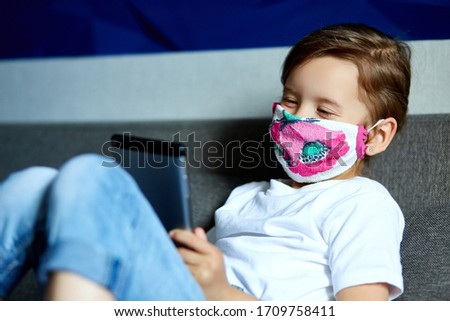 Little girl in protection mask using, play tablet or learning with video call online Stock photo © Illia