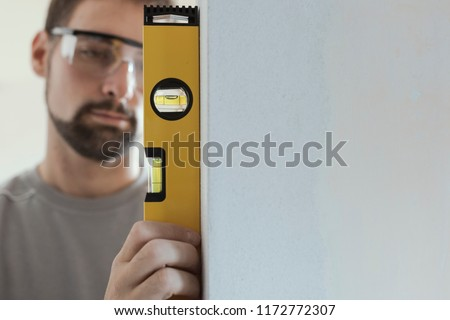 Man with spirit level checking wall Stock photo © photography33