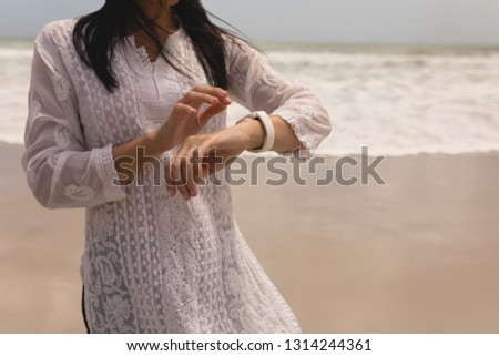 Mid section of young woman using smartwatch on beach in the sunshine Stock photo © wavebreak_media