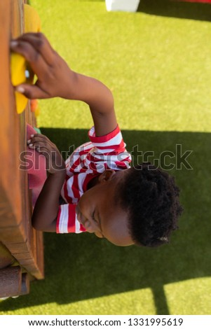 High angle view of a cute African American schoolboy climbing a wall in the school playground on a s Stock photo © wavebreak_media