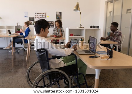 Side view of young disabled Asian male executive using digital tablet at desk in modern office. Youn Stock photo © wavebreak_media