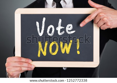 Person Pointing At Vote Now Text On Slate Stock photo © AndreyPopov
