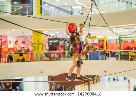 Adorable little boy enjoying his time in climbing adventure park in the mall Stock photo © galitskaya