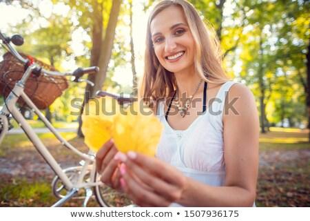 Woman stopping her bike to collect beautiful autumn foliage Stock photo © Kzenon