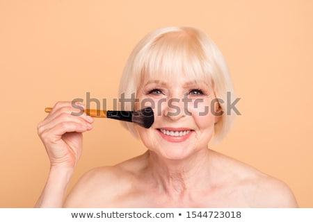 smiling senior woman with make up blush brush Stock photo © dolgachov