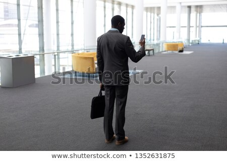 Rear view of young African-American businessman using mobile phone standing in modern office Stock photo © wavebreak_media