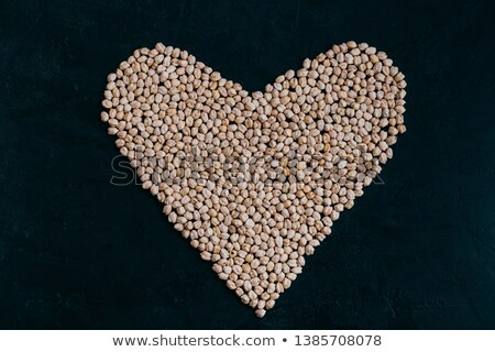 Raw chickpea in form of heart isolated on black bacground. Organic grown. Raw protein. Vegan healthy Stock photo © vkstudio