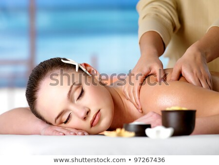 Young beautiful relaxing woman getting spa massage of shoulder in beauty salon Stock photo © galitskaya