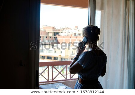 Woman in quarantine looking out of window using phone Stock photo © Kzenon