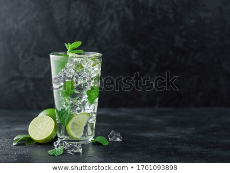 Glass of Mojito cocktail with ice cubes mint and lime on black board with spoon and fresh limes and  Stock photo © DenisMArt