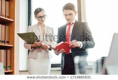 Middle Eastern and central European lawyer in their law firm reading Stock photo © Kzenon