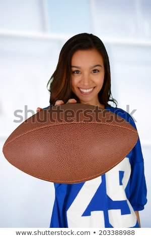 Smiling woman about to throw a football Stock photo © stryjek