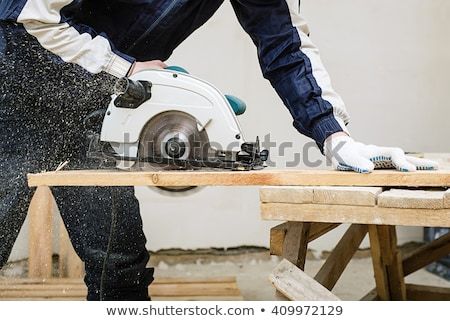Man hand holding spinning circular saw Stock photo © Olesha