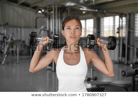 Stock photo: Military press machine woman workout at gym
