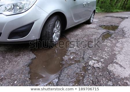 damaged road full of cracked potholes in pavement stock photo © vladacanon