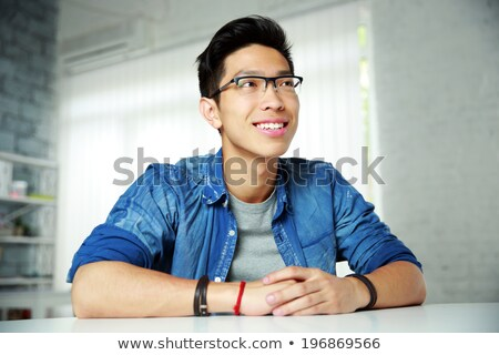 Portrait of a thoughtful asian man in glasses at office Stock photo © deandrobot