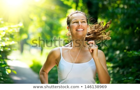 smiling sporty woman running outdoors stock photo © deandrobot