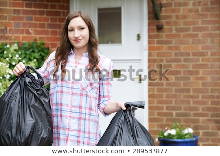 Portrait Of Woman Taking Out Garbage In Bags Stock photo © HighwayStarz