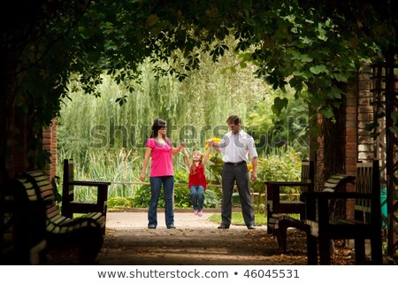 Little girl in red dress with father and mother in park in plant tunnel. Girl plays being shaken on  Stock photo © Paha_L