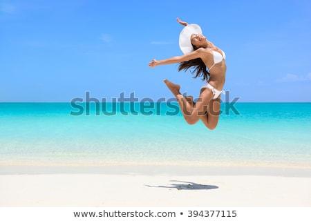 Happy bikini woman jumping of joy on white beach Stock photo © Maridav