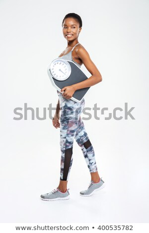 Happy fitness afro american woman holding weighing machine Stock photo © deandrobot