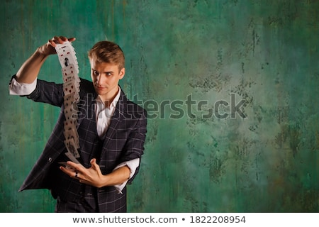 portrait of handsome young magician holding ace card stock photo © deandrobot