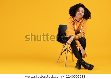 Attractive african young woman with fashion makeup sitting on chair stock photo © deandrobot