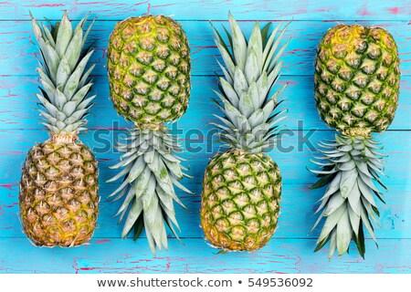 Four alternating pineapples on market table Stock photo © ozgur