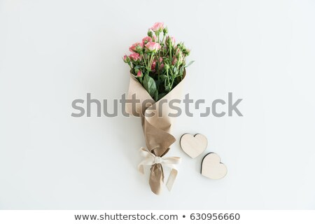 pink roses bouquet in kraft paper with two wooden hearts isolated on white with copy space wedding stock photo © lightfieldstudios