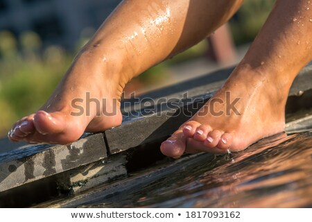 Young woman cooling her feet in fountain Stock photo © IS2
