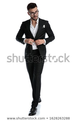 elegant man holding glasses while walking and fixing collar stock photo © feedough