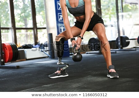 portrait of fitness disabled woman in tracksuit doing crossfit stock photo © deandrobot