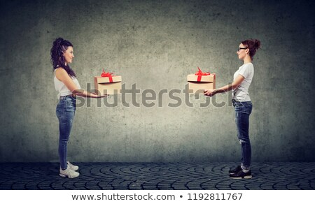 Two women exchanging with gift boxes looking happily at each other  Stock photo © ichiosea