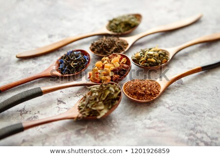 virious kinds of tea in wooden spoons on stone table stock photo © dash