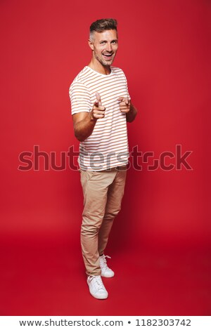 full length photo of young man in striped t shirt gesturing inde stock photo © deandrobot