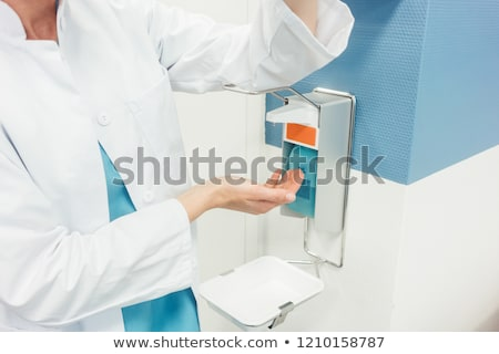 doctor cleaning and disinfecting her hands in hospital stock photo © kzenon