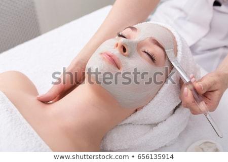 woman getting facial care by beautician at spa salon stock photo © kzenon