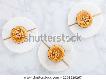 Homemade biscuit cookies with almond nuts and peanut butter on marble coasters on white kitchen tabl Stock photo © DenisMArt