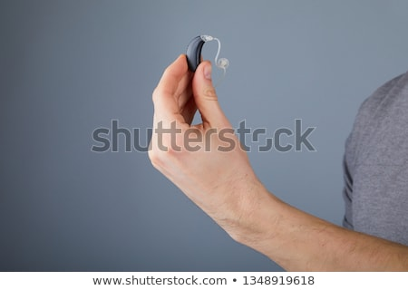Stock photo: Man Holding Hearing Aid