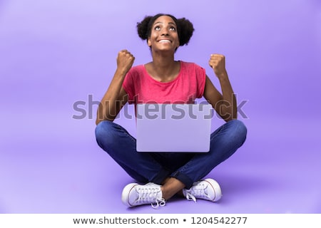 Photo of amusing african american woman smiling and using silver Stock photo © deandrobot