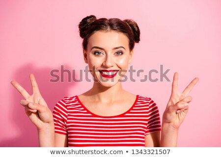 Portrait of caucasian funny girl with two buns smiling and looki Stock photo © deandrobot