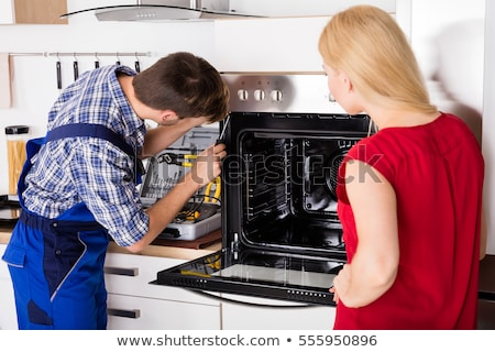 young repairman repairing oven on kitchen worktop stock photo © andreypopov