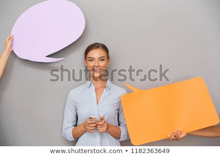 woman standing over grey wall background with speech bubbles chatting by mobile phone stock photo © deandrobot