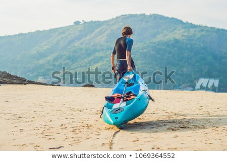 young man carrying his kayak along the shore stock photo © galitskaya